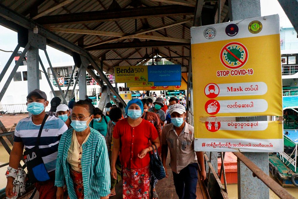 FILE - In this July 27, 2021, file photo, ferry passengers wearing face masks to help curb the spread of the coronavirus walk past a