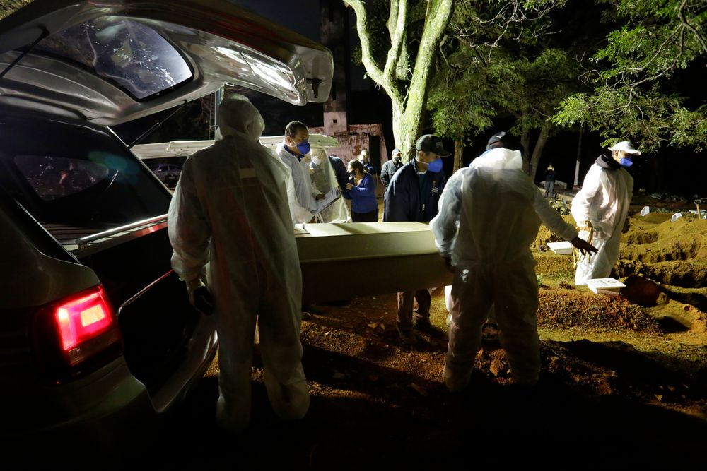 Cemetery workers carry the coffin of a COVID-19 victim to his grave during a nighttime funeral at the Vila Formosa cemetery in Sao Paulo, Brazil, Wednesday, April 28, 2021. (AP Photo/Nelson Antoine)