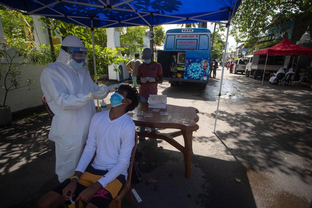 A Sri Lankan health officer collects a swab sample to test for COVID-19 in Colombo, Sri Lanka, Tuesday, June 29, 2021. (AP Photo/Eranga Jayawardena)