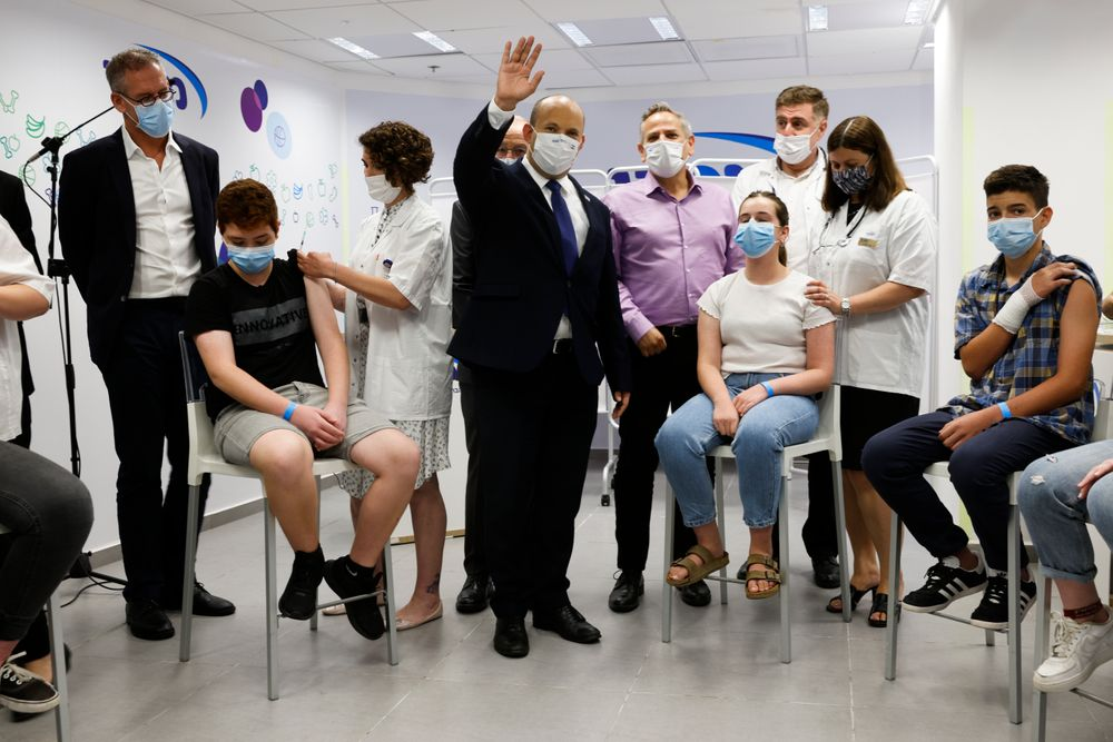 Israeli Prime Minister Naftali Bennett, center, gestures as he stands next to youths during his visit to a Maccabi healthcare maintenance organisation (HMO) outlet which offers vaccinations against the coronavirus disease (COVID-19) in Holon, near Tel Aviv, Israel  Tuesday, June 29, 2021. (Amir Cohen/Pool Photo via AP)