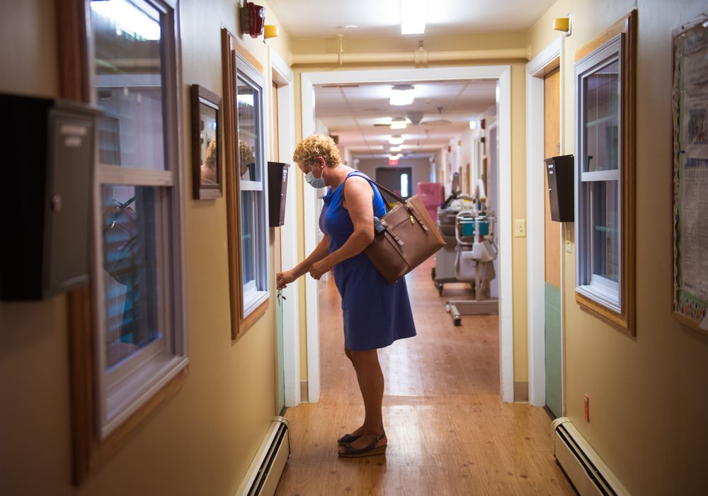 Anna Zambrano unlocks the door to her office after arriving at work to Eastgate Nursing and Rehabilitation Center on a recent muggy August morning. A patient floor is just beyond her office.