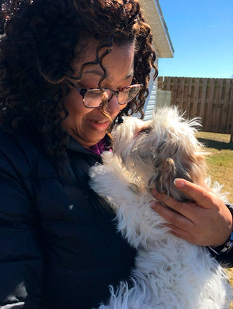 """In a photo provided by Candace Croney, Croney holds her dog, Desi, in April 2019, in Indiana. """"If we think how much time most of our pets prior to the pandemic typically would spend without people around to 24 hours a day, seven days a week, it's quite a lot,"""" says Croney, a Purdue University professor who teaches about animal behavior. (Courtesy of Candace Croney via AP)"""