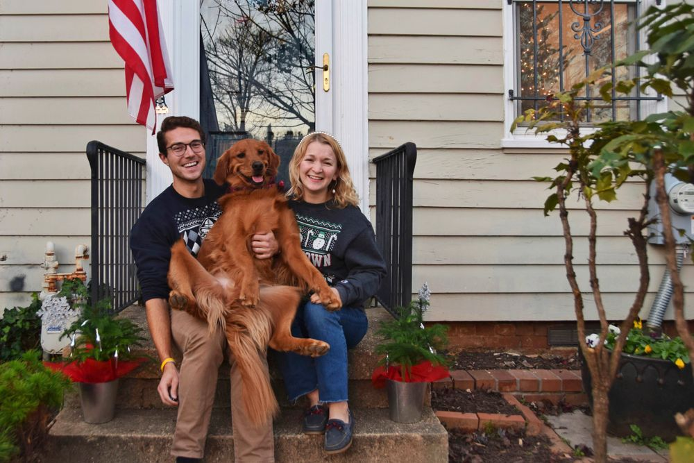 """In this photo provided by Olivia Hinerfeld, Olivia Hinerfeld poses with her boyfriend, Ryan Shymansky, and their golden retriever Lincoln on Dec. 6, 2020, in Washington. Jealous of the attention that Hinerfeld is paying to her video conference call, Lincoln,will fetch """"the most disgusting"""" tennis ball he can find from his toy crate to drop into the lap of the Georgetown University Law School student. (Olivia Hinerfeld via AP)"""