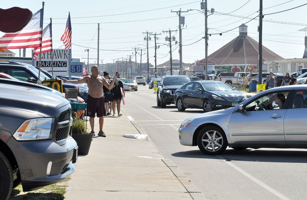 Pete Duglenski guides cars into a parking lot on Atlantic Avenue in Westerly on Saturday, July 18, 2020.