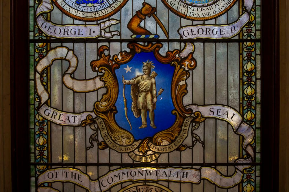 "An image of a glass-stained ""Seal of the Commonwealth"" located at the top of the grand staircase inside the State House."