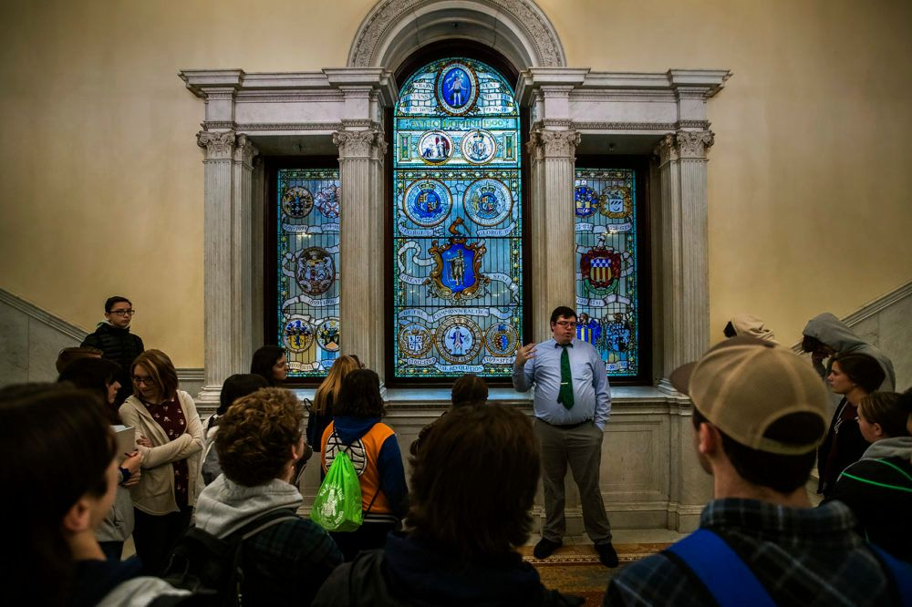 """A tour group inside the Massachusetts State House is shown a stained glass display with the """"Seal of the Commonwealth"""" located at the top of the grand staircase."""