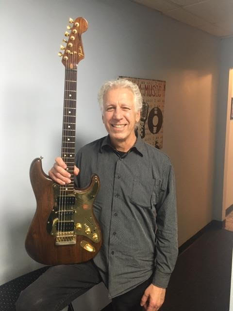 Steve Young holding his guitar.