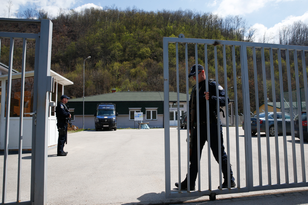 Kosovo police officer secures the area of a detention center where authorities brought back from Syria 110 Kosovar citizens, mostly women and children in the village of Vranidol on Sunday, April 20, 2019.  Four suspected fighters have been arrested, but other returnees will be cared for, before being sent to homes over the coming days according to Justice Minister Abelard Tahiri.  (AP Photo/Visar Kryeziu)