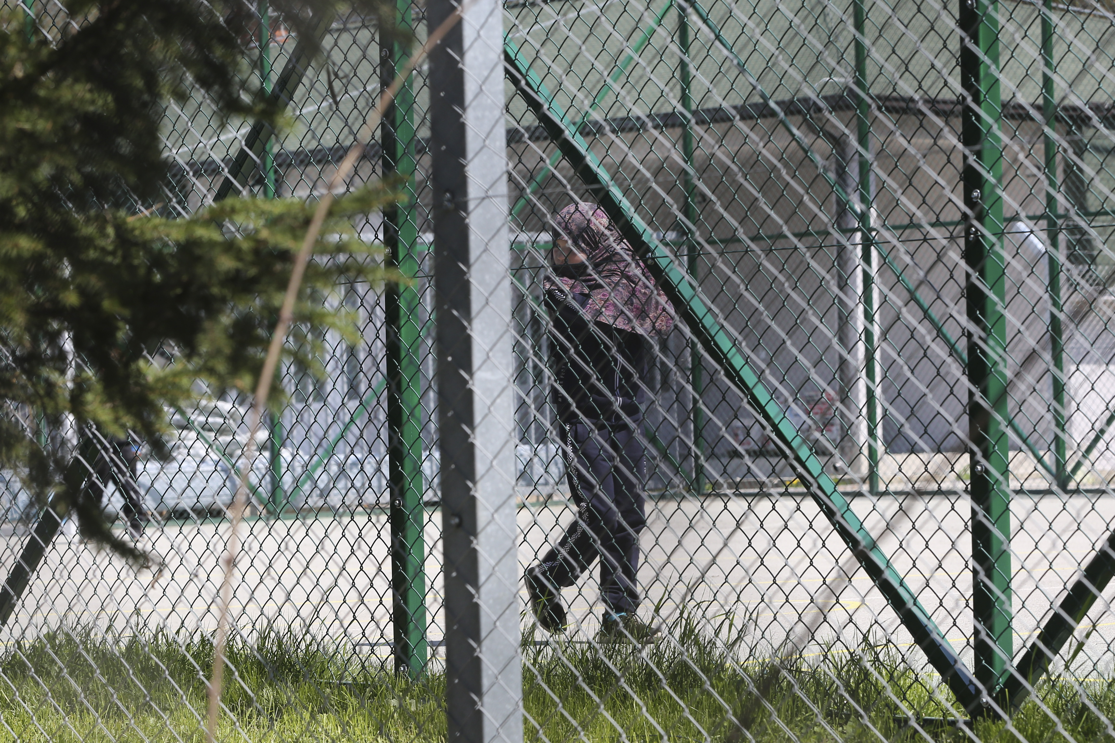 A girl walks inside a detention center where authorities brought back from Syria 110 Kosovar citizens, mostly women and children in the village of Vranidol on Sunday, April 20, 2019.  Four suspected fighters have been arrested, but other returnees will be cared for, before being sent to homes over the coming days according to Justice Minister Abelard Tahiri. (AP Photo/Visar Kryeziu)