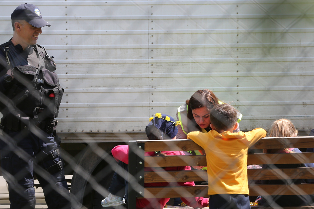 A police officer plays with a group of children inside a detention center where authorities have brought back from Syria 110 Kosovar citizens, mostly women and children in the village of Vranidol on Sunday, April 20, 2019.  Four suspected fighters have been arrested, but other returnees will be cared for, before being sent to homes over the coming days, according to Justice Minister Abelard Tahiri.(AP Photo/Visar Kryeziu)