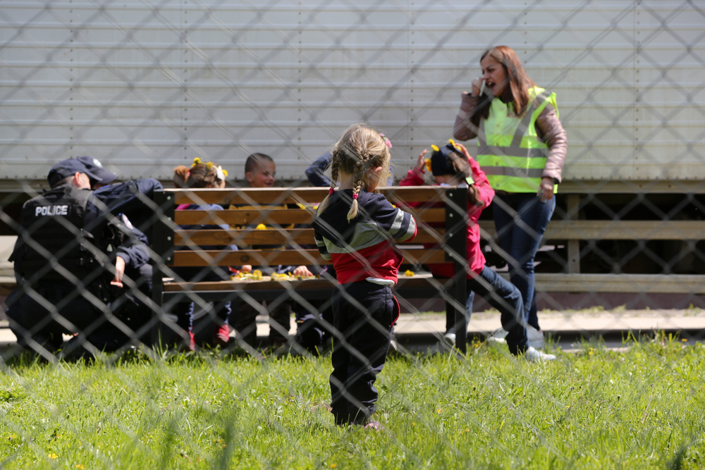 Police officers play with a group of children at a detention center where authorities have brought back from Syria 110 Kosovar citizens, mostly women and children in the village of Vranidol on Sunday, April 20, 2019.  Four suspected fighters have been arrested, but other returnees will be cared for, before being sent to homes over the coming days, according to Justice Minister Abelard Tahiri.(AP Photo/Visar Kryeziu)