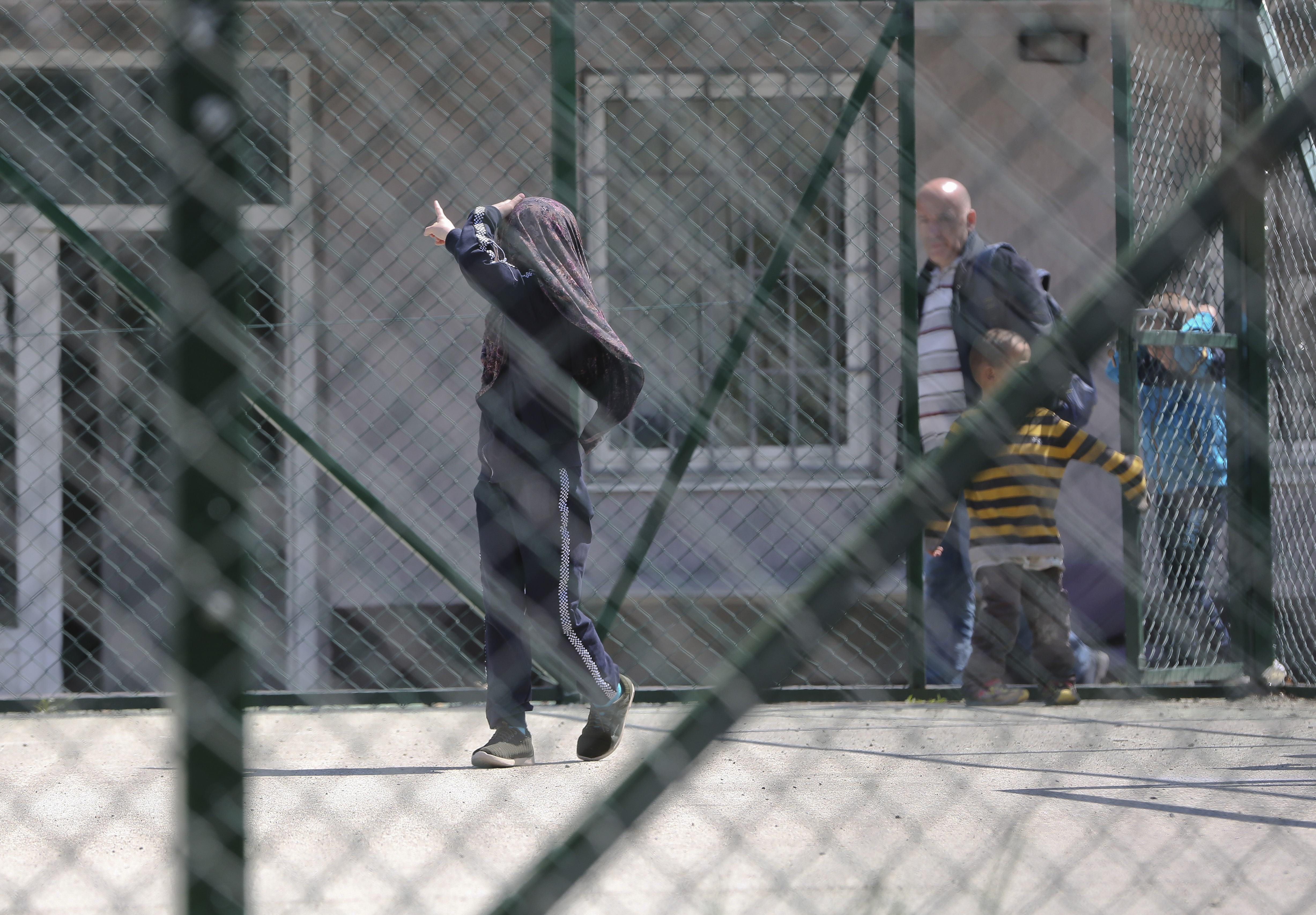 Group of children walk at a detention center where authorities have brought back from Syria 110 Kosovar citizens, mostly women and children in the village of Vranidol on Sunday, April 20, 2019.  Four suspected fighters have been arrested, but other returnees will be cared for, before being sent to homes over the coming days, according to Justice Minister Abelard Tahiri. (AP Photo/Visar Kryeziu)