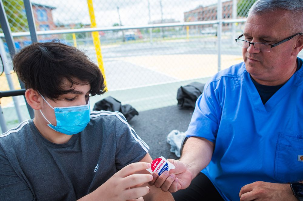 John Pizzo, a public health nurse for the Rhode Island National Guard hands a sticker to Victor Urizar, 15, of Providence after giving him a COVID-19 vaccine at Bucklin Park in August.