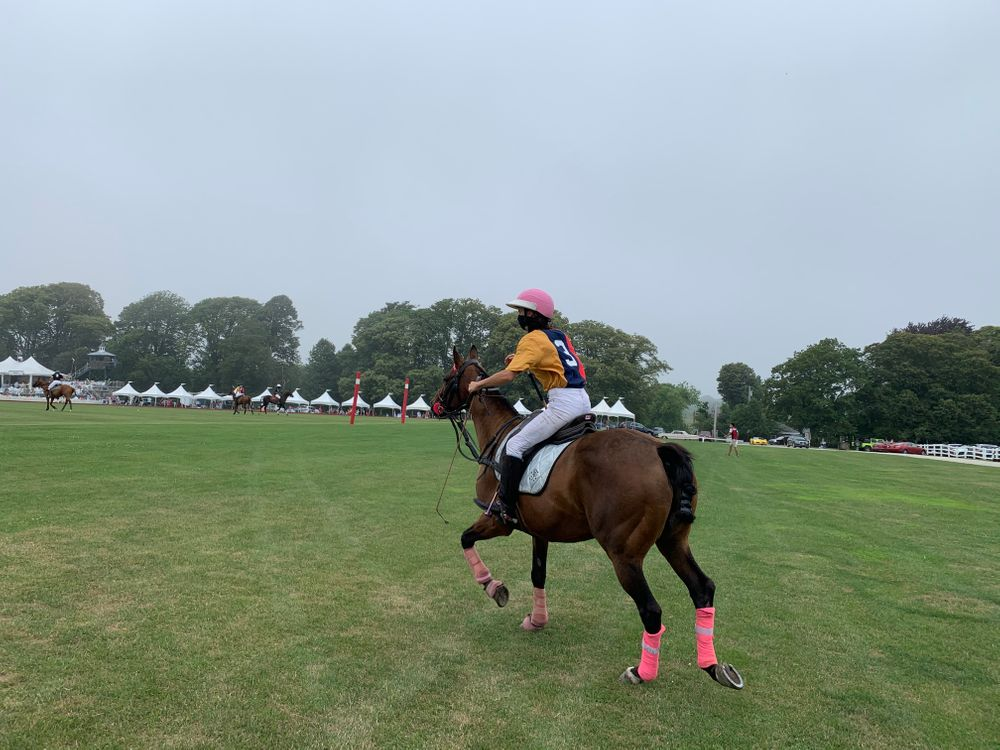 A player on the Astors team rides onto the polo field.