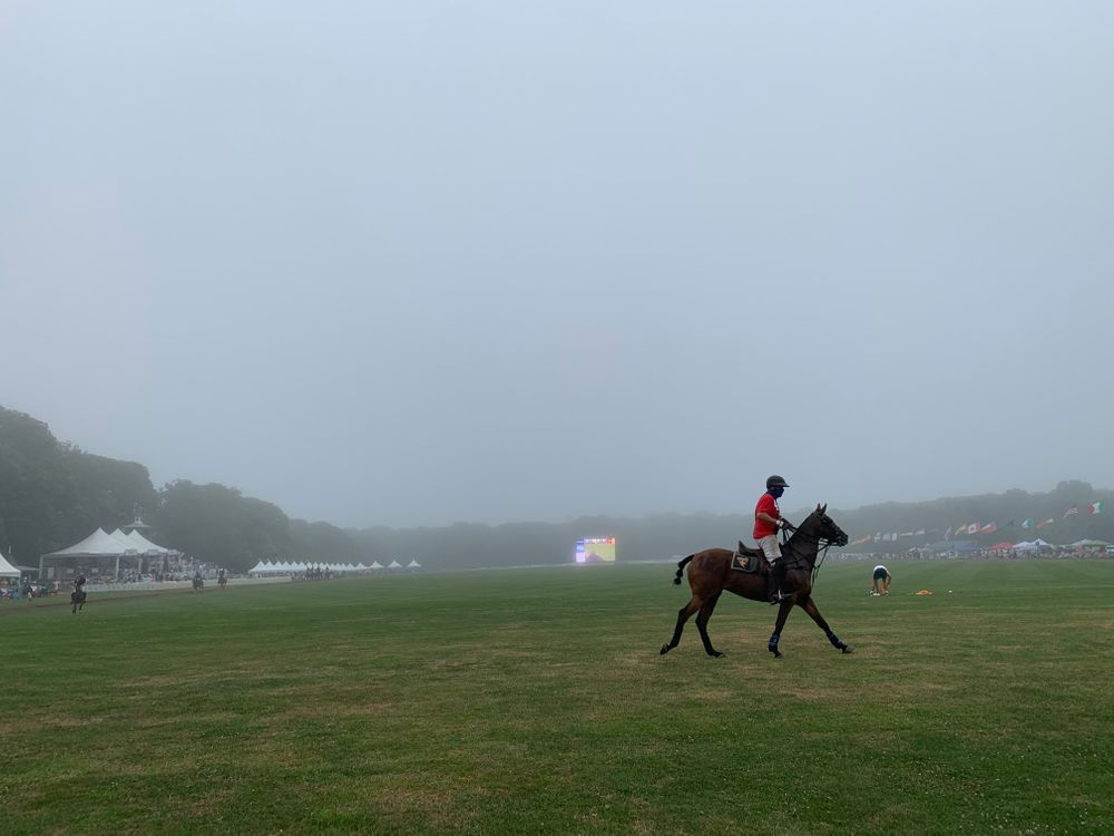 A player takes a final lap as fog covers the polo field at Glen Farm.