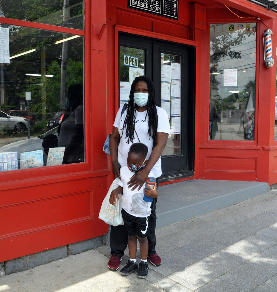Charlene Traynum with her son outside of Jordan New Style Barbershop in Wakefield.