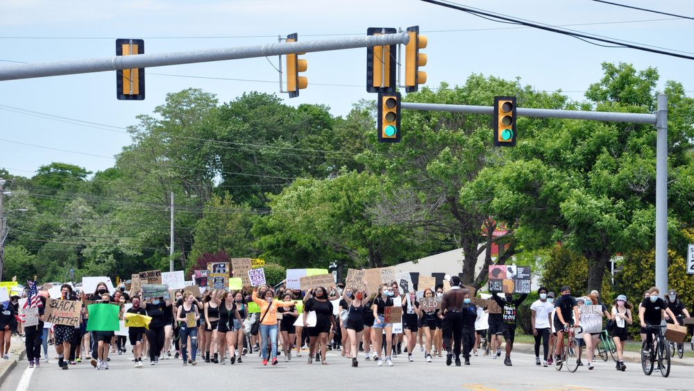 Protesters march down Kingstown Road in South Kingstown.