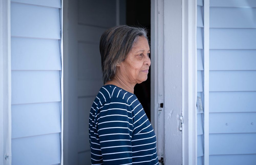 Gertrudis Pena outside her home in Providence