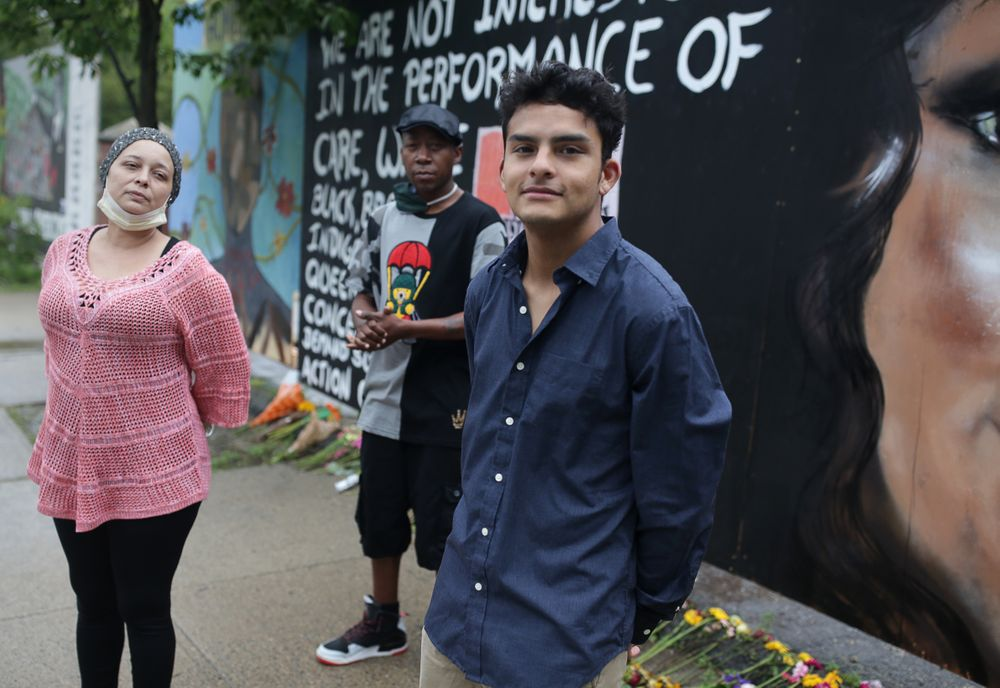 Shevon L. Young, left, and her boyfriend Darryl K. Jordan Jr., middle, stand in front of murals painted on boarded-up storefront windows, along with Michael Tuberquia, right.
