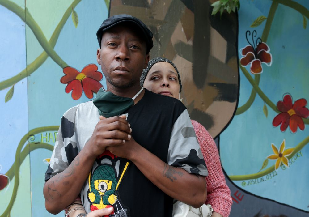Darryl K. Jordan Jr., front, with his girlfriend, Shevon L. Young, in front of a mural painted on a boarded-up storefront window in Providence.