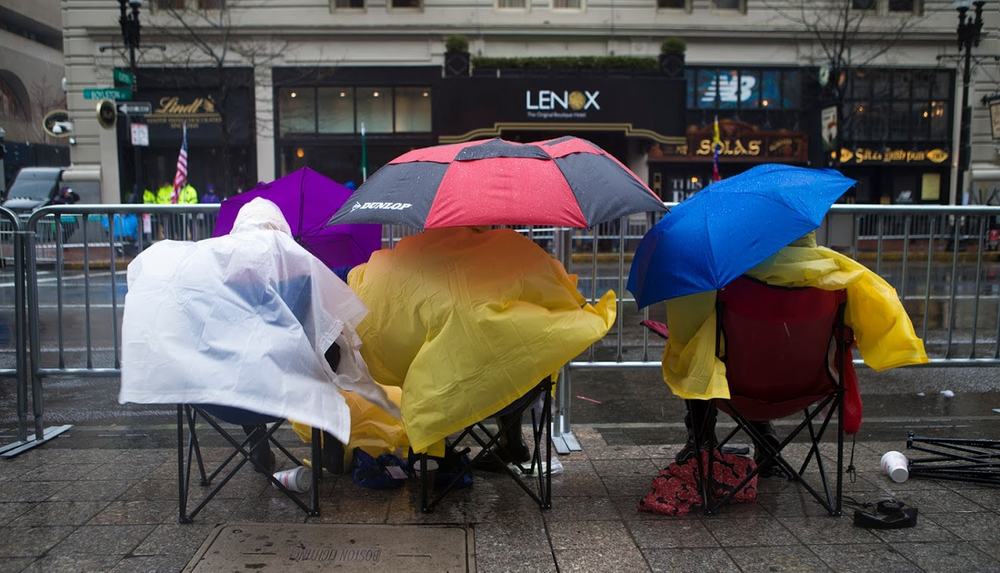 Spectators camped out in the wind and rain along Boylston St.