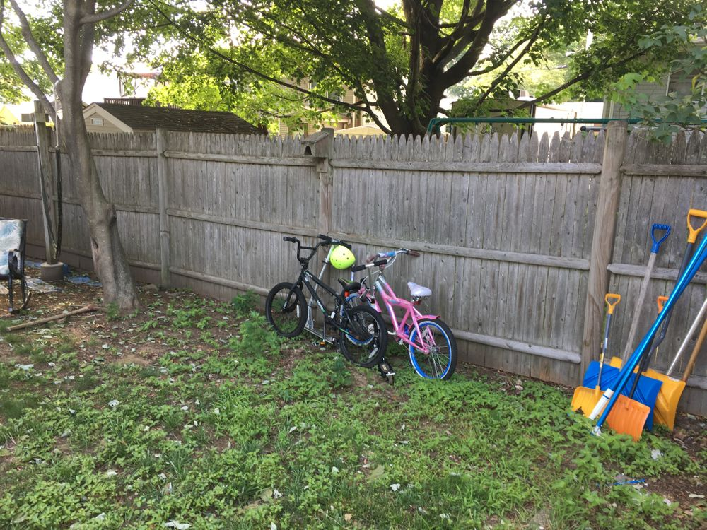 Two bikes lean against the fence in Mary's backyard.