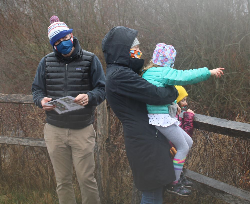 A family pauses to look out from an observation deck at birds on the Acushnet River at the Sawmill in Acushnet.