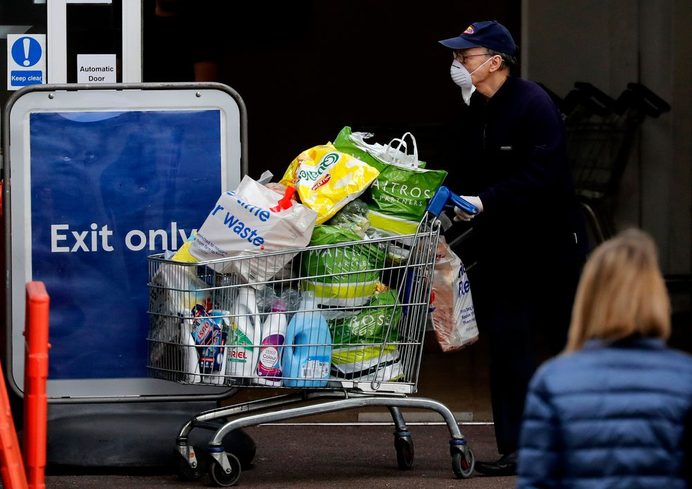 Shoppers wear face masks to protect against the coronavirus outbreak as they do their weekend shopping at a supermarket in London, Friday, April 17, 2020. The highly contagious COVID-19 coronavirus has impacted on nations around the globe, many imposing self isolation and exercising social distancing when people move from their homes.(AP Photo/Frank Augstein)