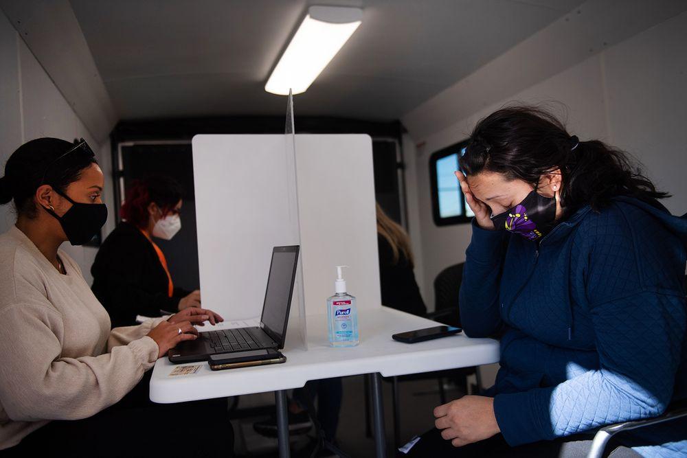 Karen Zuniga (left) helps Elsa Lopez (right) register for a COVID-19 vaccination inside ONE Neighborhood Builders' mobile clinic.