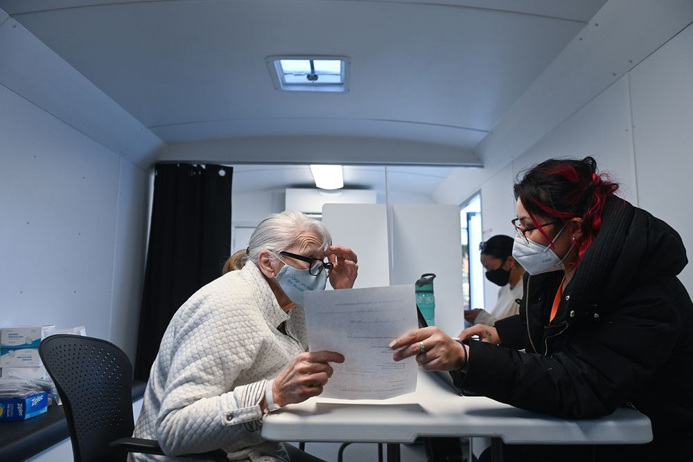 Jean Philip (left) listens as community health worker Karen Zuniga explains her clinic options inside a mobile health clinic run by the nonprofit ONE Neighborhood Builders.