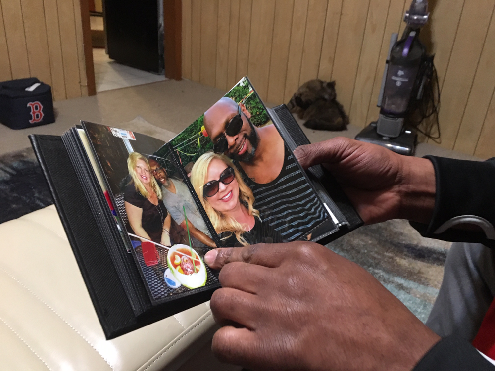 Kevin White looks at a photo album with pictures of him and his fiance, Rena Fleury, who died of a cardiac arrest last August.