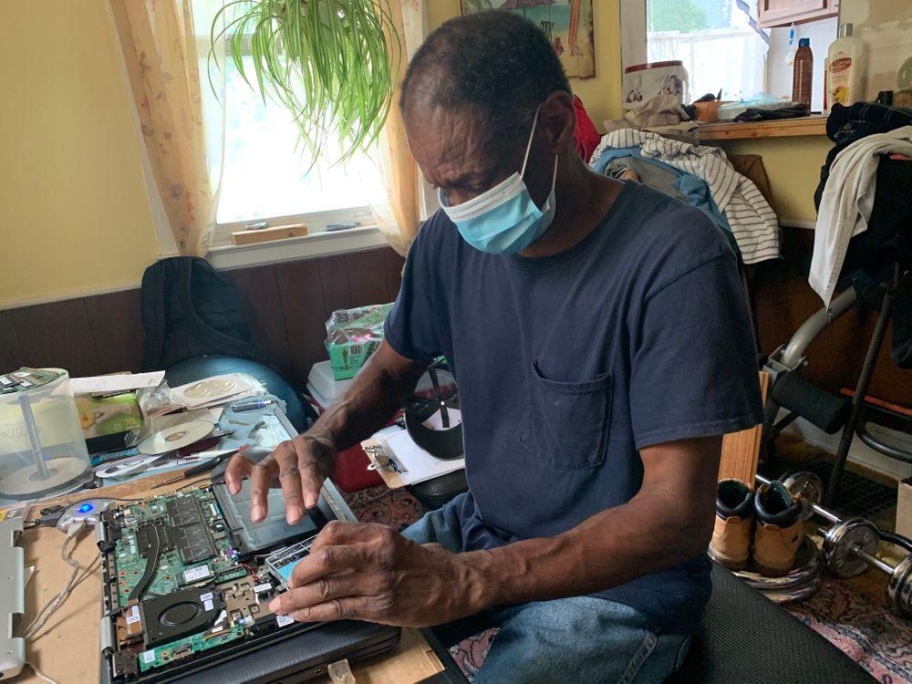 Harry Jones repairs a client's broken laptop in his home office.