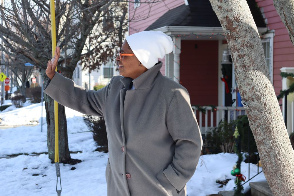Cynthia Moreino waves to a neighbor nearby her home in the North End.