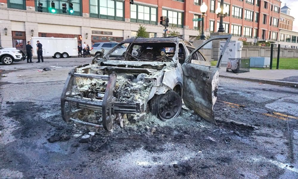 The remains of a police cruiser set on fire by rioters near the Providence Place Mall