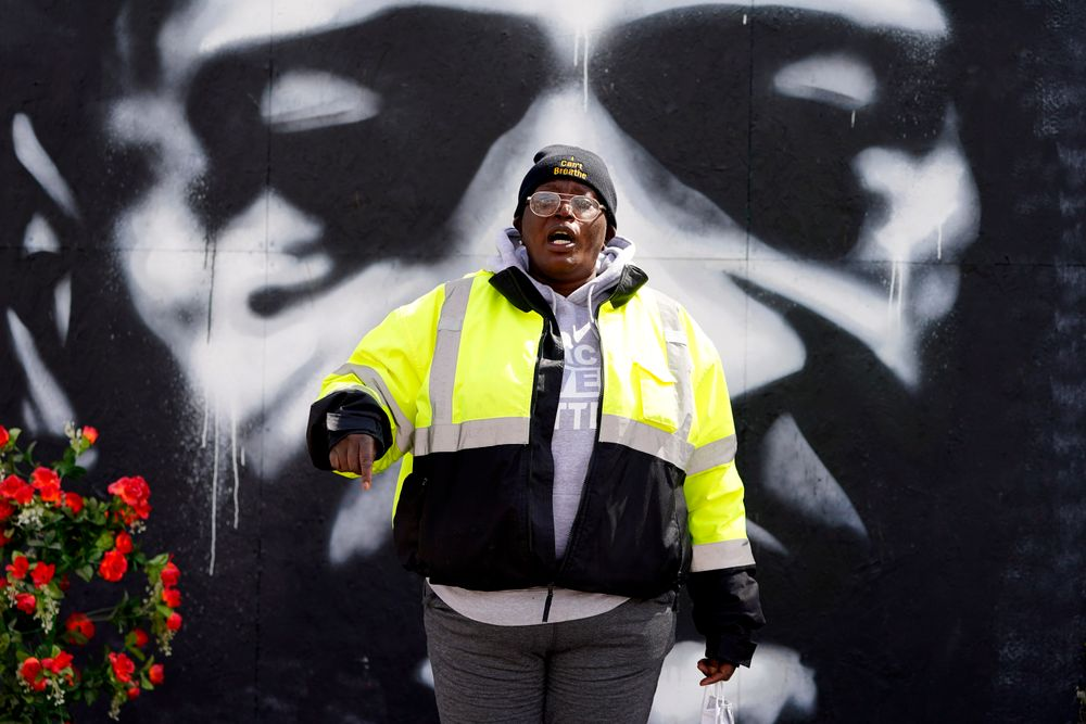 An organizer speaks in front of a mural depicting George Floyd's likeness at George Floyd Square, Wednesday, April 21, 2021, in Minneapolis, a day after former Minneapolis police Officer Derek Chauvin was convicted on all counts for the 2020 death of Floyd. (AP Photo/Julio Cortez)