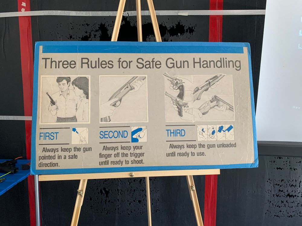 A poster board at the front of the Newport Rifle Club classroom displays the National Rifle Association's three rules for safe gun handling.
