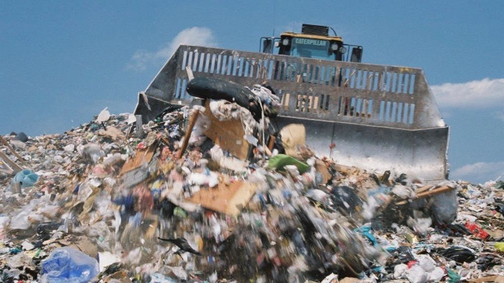 A loader pushes trash onto the active face of the landfill