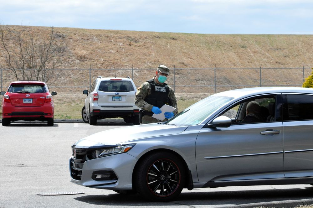 A National Guard member speaks to an out-of-state motorist at a checkpoint on Route 1 in Westerly, R.I., Wednesday, April 1, 2020.