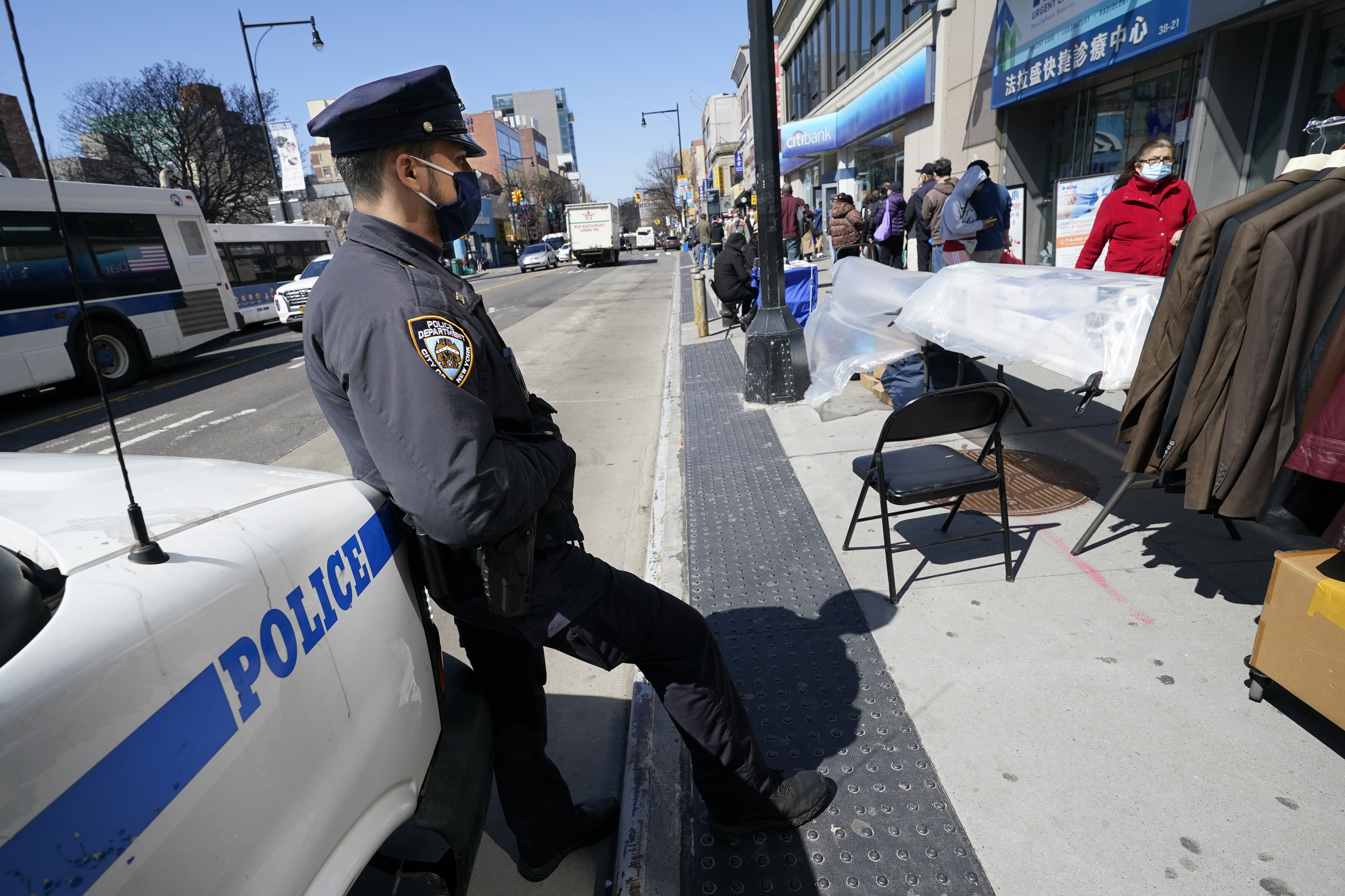 New York Police Department Officer Rodney Hierro keeps an eye on pedestrians walking on Main Street in Flushing, a heavily Asian neighborhood, Tuesday, March 30, 2021, in the Queens borough of New York. A vicious attack on an Asian American woman Monday near New York City's Times Square is drawing widespread condemnation and raising alarms about the failure of bystanders to intervene amid a rash of anti-Asian violence across the U.S. (AP Photo/Kathy Willens)