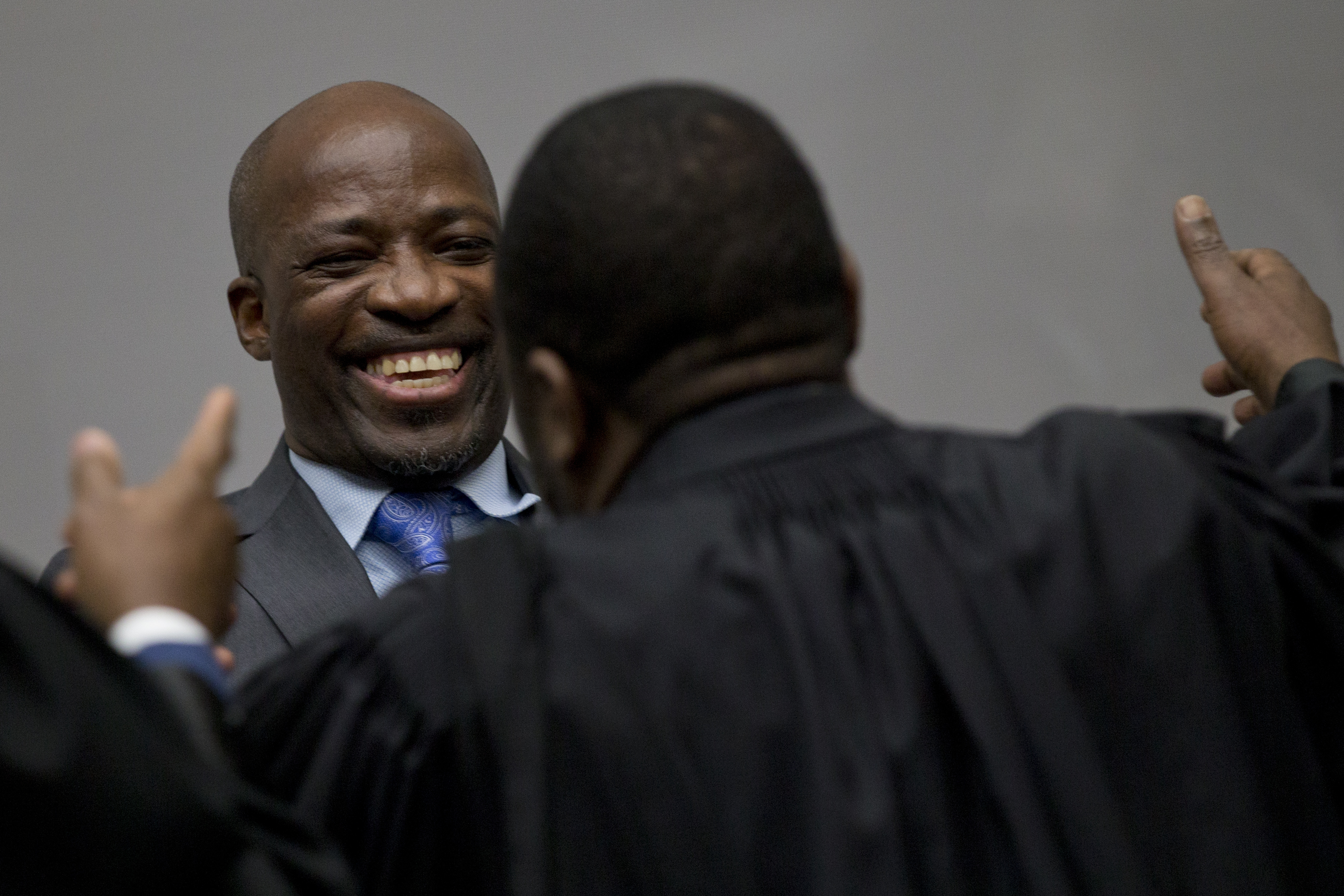 Charles Ble Goude hugs his legal team as he and former Ivory Coast President Laurent Gbagbo enter the courtroom of the International Criminal Court in The Hague, Netherlands, Tuesday, Jan. 15, 2019, where judges were expected to issue rulings on requests by Gbagbo and ex-government minister Goude to have their prosecutions thrown out for lack of evidence. (AP Photo/Peter Dejong, Pool)