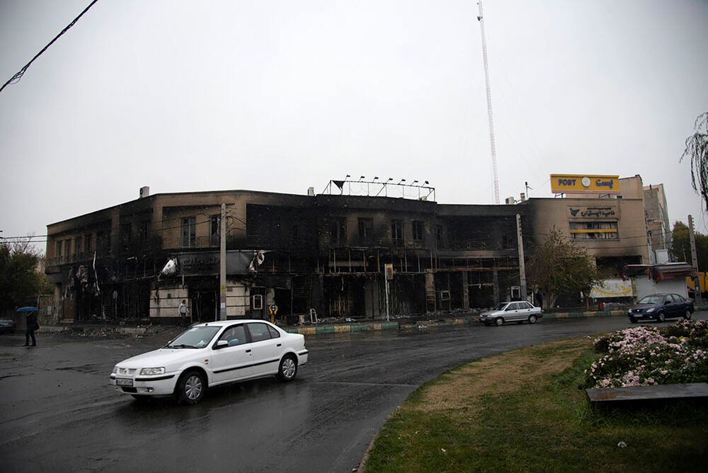 In this photo taken Monday, Nov. 18, 2019, and released by the Iranian Students' News Agency, ISNA, cars drive past a building which burned during protests that followed the authorities' decision to raise gasoline prices, in the city of Karaj, west of the capital Tehran, Iran. An article published Tuesday in Keyhan, a hard-line newspaper in Iran suggested that those who led violent protests will be executed by hanging as the unrest continues. (Masoume Aliakbar/ISNA via AP)