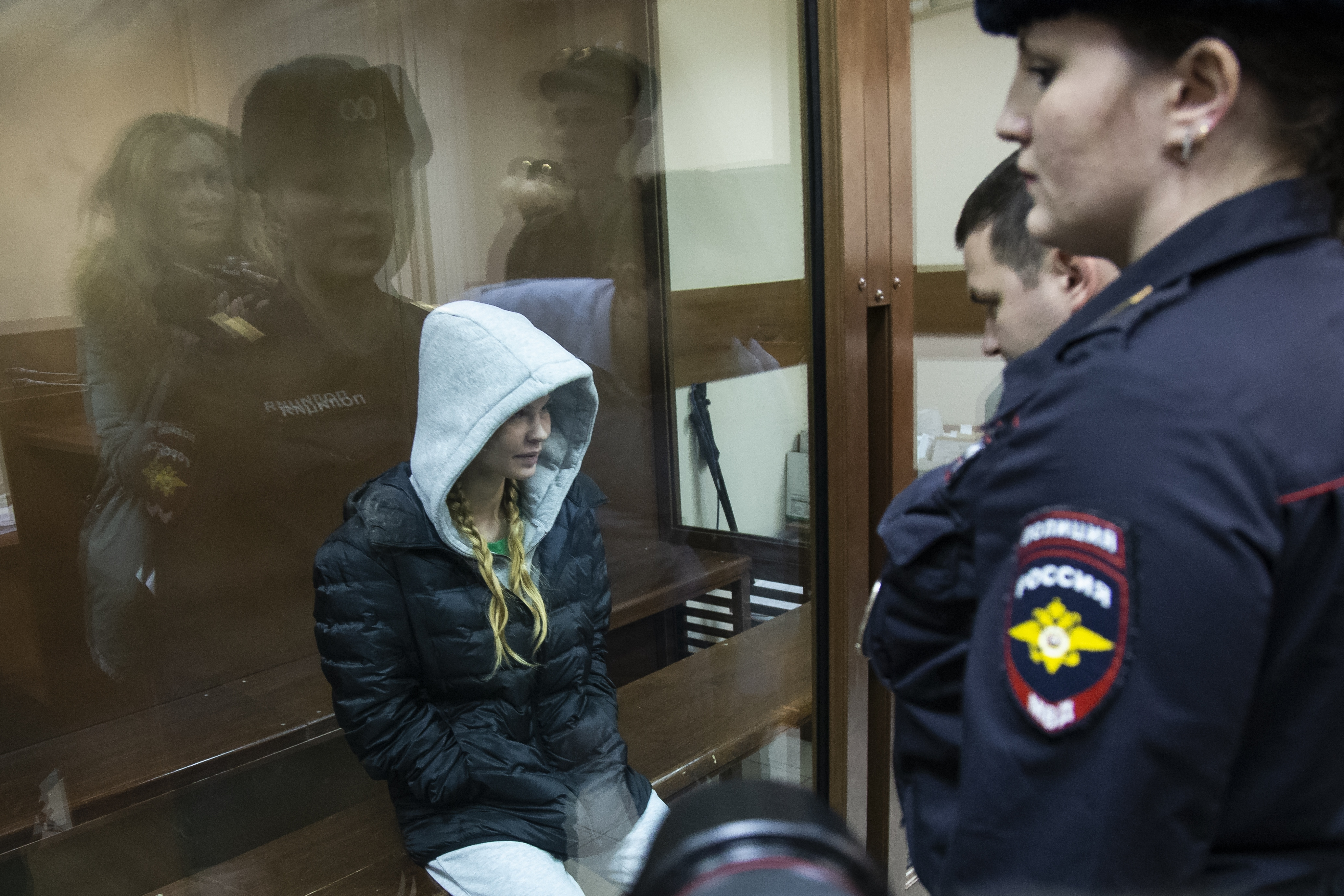 Anastasia Vashukevich, also known on social media as Nastya Rybka, left, sits in a cage in the court room in Moscow, Russia, Saturday, Jan. 19, 2019. A Belarusian model who claimed last year that she had evidence of Russian interference in the election of Donald Trump as U.S. president was arrested immediately upon her arrival in Moscow on Thursday following deportation from Thailand. (AP Photo/Alexander Zemlianichenko)