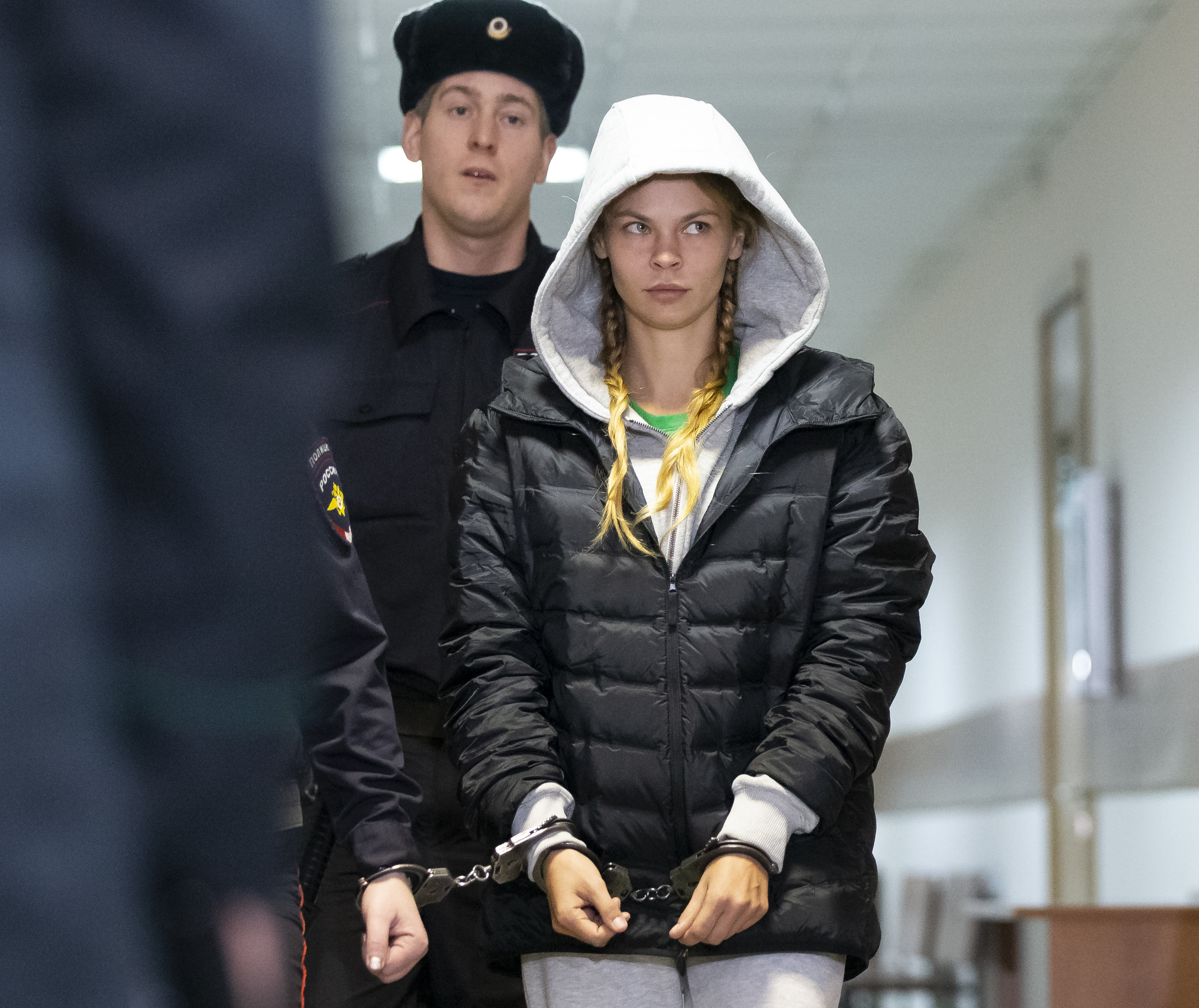 Anastasia Vashukevich, also known on social media as Nastya Rybka is escorted in the court room in Moscow, Russia, Saturday, Jan. 19, 2019. The Belarusian model Vashukevich, who claimed last year that she had evidence of Russian interference in the election of Donald Trump as U.S. president, was arrested upon arrival in Moscow on Thursday following deportation from Thailand. (AP Photo/Alexander Zemlianichenko)