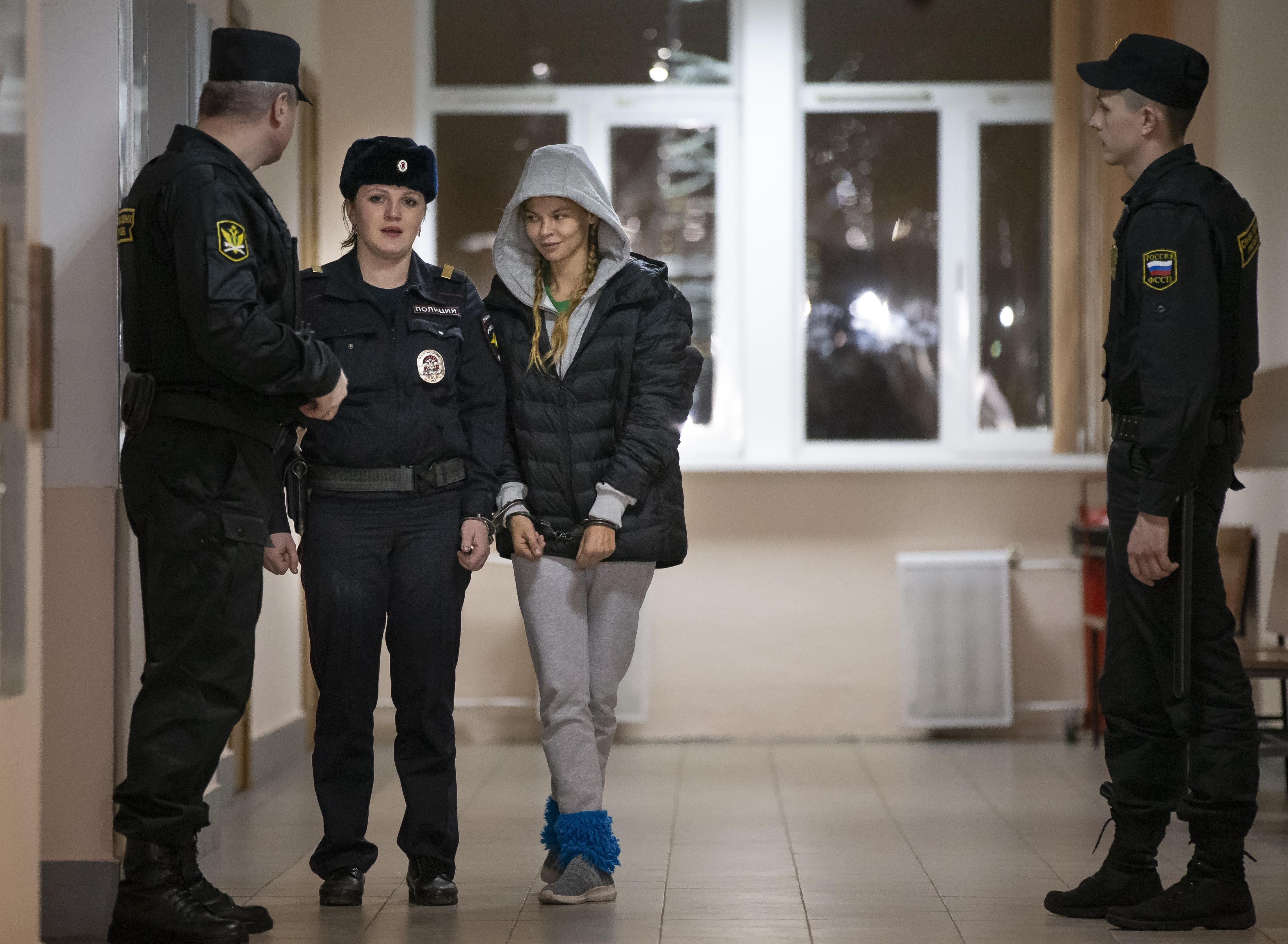 Anastasia Vashukevich, also known on social media as Nastya Rybka, center, is escorted in the court room in Moscow, Russia, Saturday, Jan. 19, 2019. A Belarusian model who claimed last year that she had evidence of Russian interference in the election of Donald Trump as U.S. president was arrested immediately upon her arrival in Moscow on Thursday following deportation from Thailand. (AP Photo/Alexander Zemlianichenko)