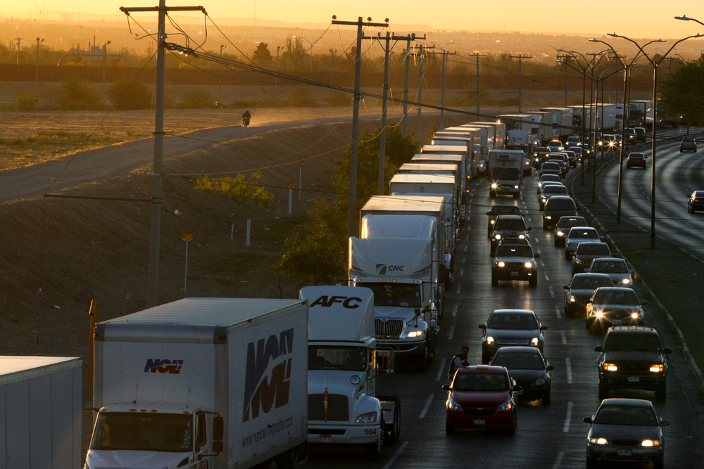 FILE- In this April 9, 2019, file photo, trucks wait to cross the border with the U.S. in Ciudad Juarez, Mexico.  In a surprise announcement that could compromise a major trade deal, President Donald Trump announced Thursday that he is slapping a 5% tariff on all Mexican imports to pressure the country to do more to crack down on the surge of Central American migrants trying to cross the U.S. border. (AP Photo/Christian Torres, File)
