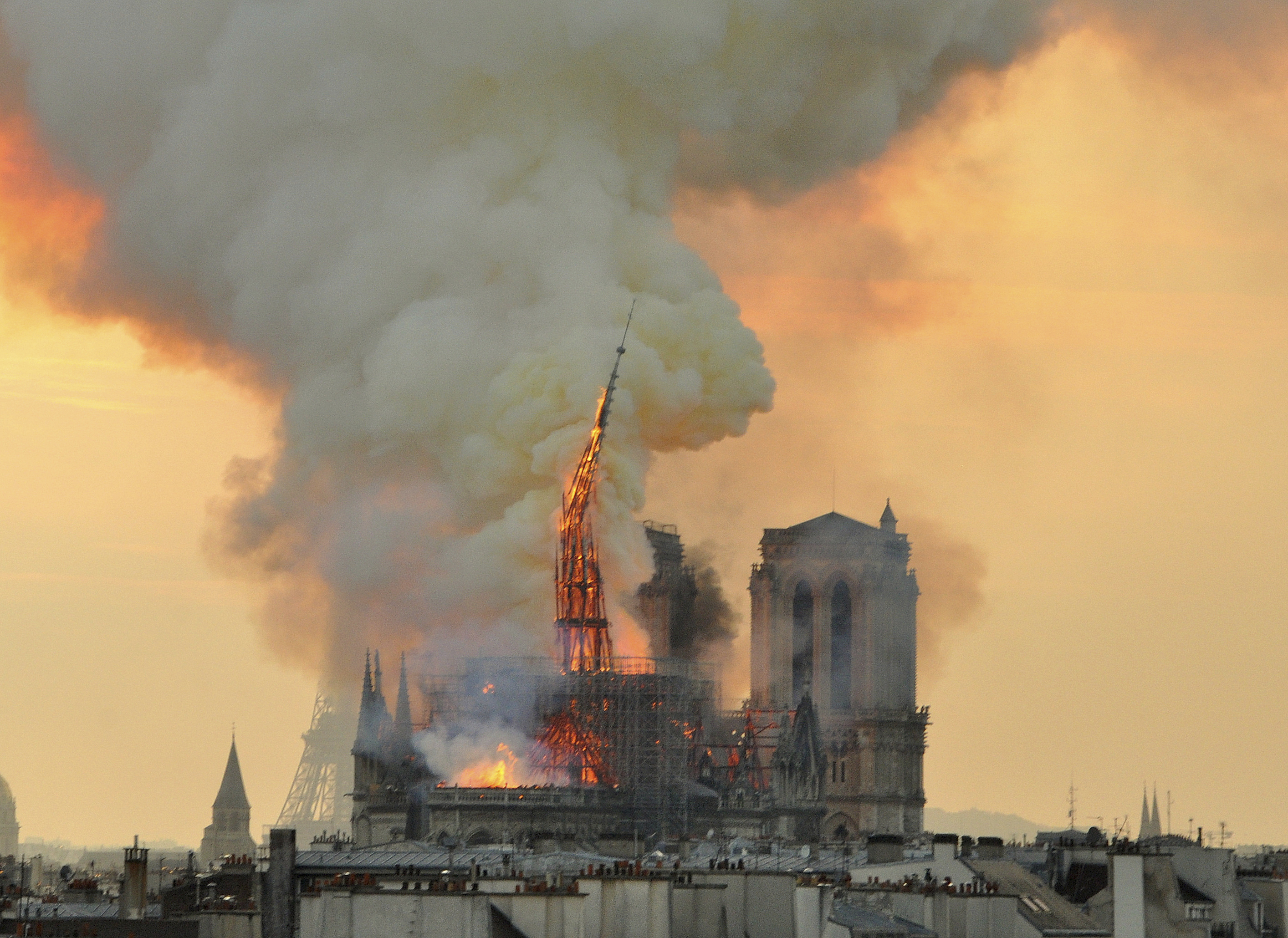 In this image made available on Tuesday April 16, 2019 flames and smoke rise from the blaze as the spire starts to topple on Notre Dame cathedral in Paris, Monday, April 15, 2019. An inferno that raged through Notre Dame Cathedral for more than 12 hours destroyed its spire and its roof but spared its twin medieval bell towers, and a frantic rescue effort saved the monument's