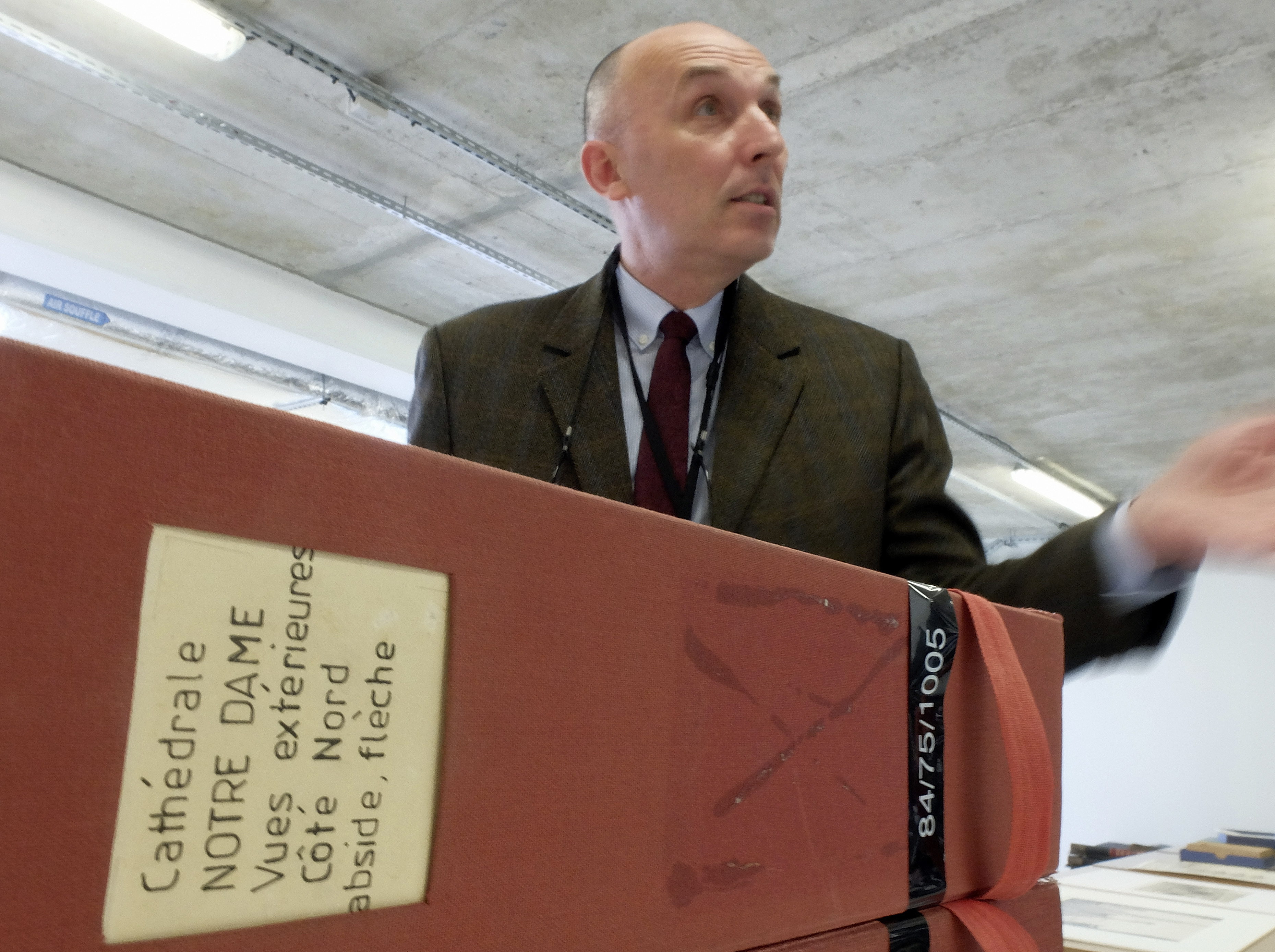 Jean-Charles Forgeret poses with files related to Notre Dame cathedral in Charenton le Pont, outside Paris, Thursday, April 18, 2019. The reconstruction of Paris' Notre Dame Cathedral will rely on part on extensive plans drawn up in the 19th century for its last big renovation. Forgeret noted that the last restoration took 20 years, and cast doubt on the French president's 5-year deadline on fixing Notre Dame this time. (AP Photo/Nicolas Garriga)