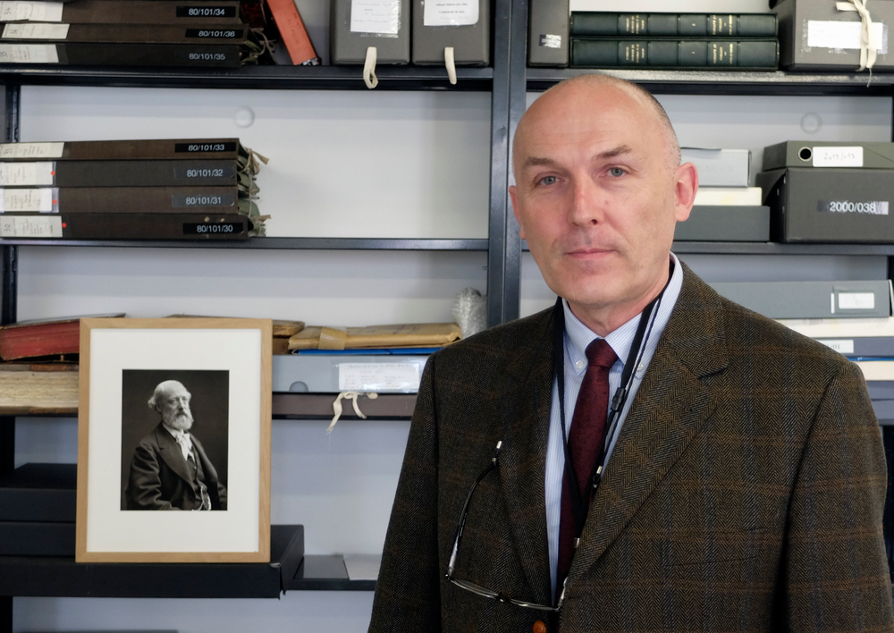 Jean-Charles Forgeret poses next to photograph of Eugene Emmanuel Viollet-le-Duc, the renowned architect who designed the spire that was added to the medieval cathedral in the 19th century, in Charenton le Pont, outside Paris, Thursday, April 18, 2019. The reconstruction of Paris' Notre Dame Cathedral will rely on part on extensive plans drawn up in the 19th century for its last big renovation. Forgeret noted that the last restoration took 20 years, and cast doubt on the French president's 5-year deadline on fixing Notre Dame this time. (AP Photo/Nicolas Garriga)