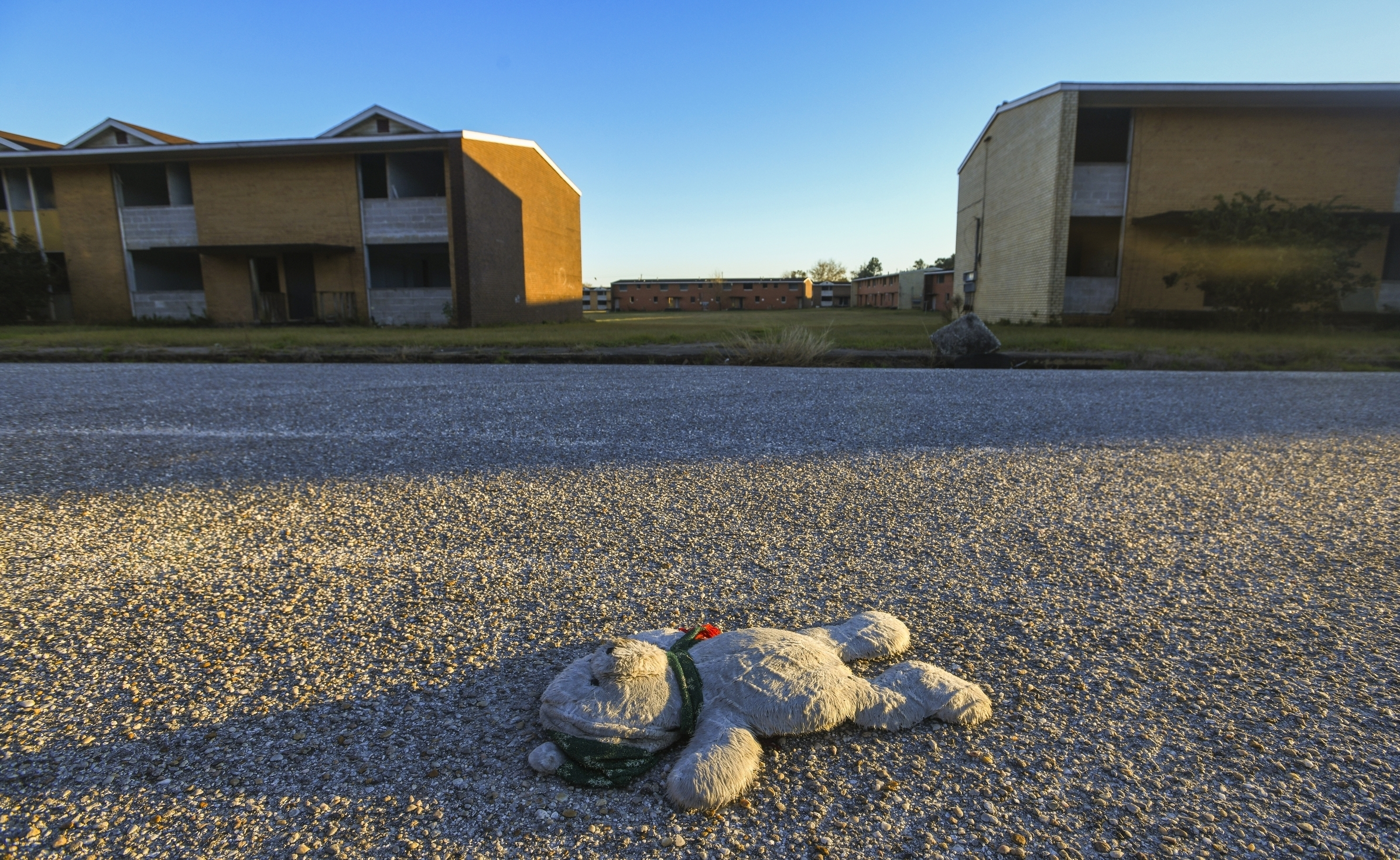 A teddy bear lies in the middle of Franklin Drive in what's known as the Africatown's Happy Hills community in Mobile, Ala., on Tuesday, Jan. 29, 2019. The Josephine Allen housing project stands abandoned in the background. (AP Photo/Julie Bennett)