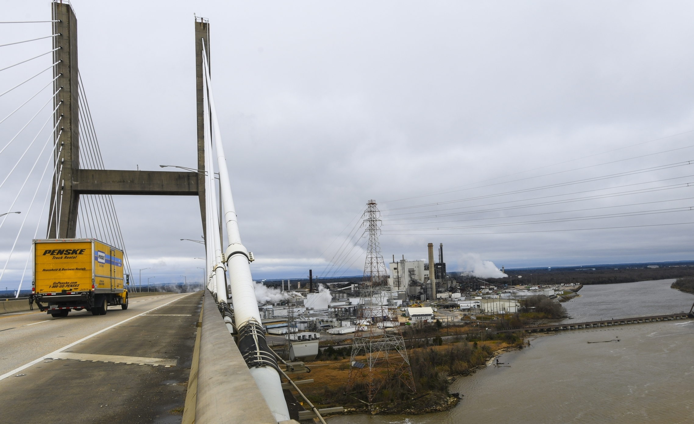Industrial development occupies the Mobile Riverfront under the Cochrane-Africatown bridge near Mobile, Ala., on Tuesday, Jan. 29, 2019. Industrial development choked off access to the Mobile River and Chickasaw Creek, where generations in Africatown caught crabs and fish. Factories now occupy land that once held modest homes surrounded by gardens, fruit trees and clucking chickens. The population has plummeted; many of the remaining homes are boarded up and rotting. (AP Photo/Julie Bennett)